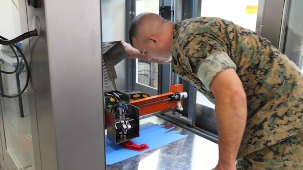 Gunnery Sgt. Doug McCue, a machinist with the 2nd Maintenance Battalion at Camp Lejeune, North Carolina, demonstrates the capabilities of a large-build 3-D printer in the X-FAB Facility Aug. 1. The X-FAB, or Expeditionary Fabrication, Facility is a self-contained, transportable additive manufacturing lab comprised of a 20-by-20-foot shelter, 3-D printers, a scanner and computer-aided design software system that can be used to fabricate repair and replacement parts in the field. (U.S. Marine Corps photo by Kaitlin Kelly)