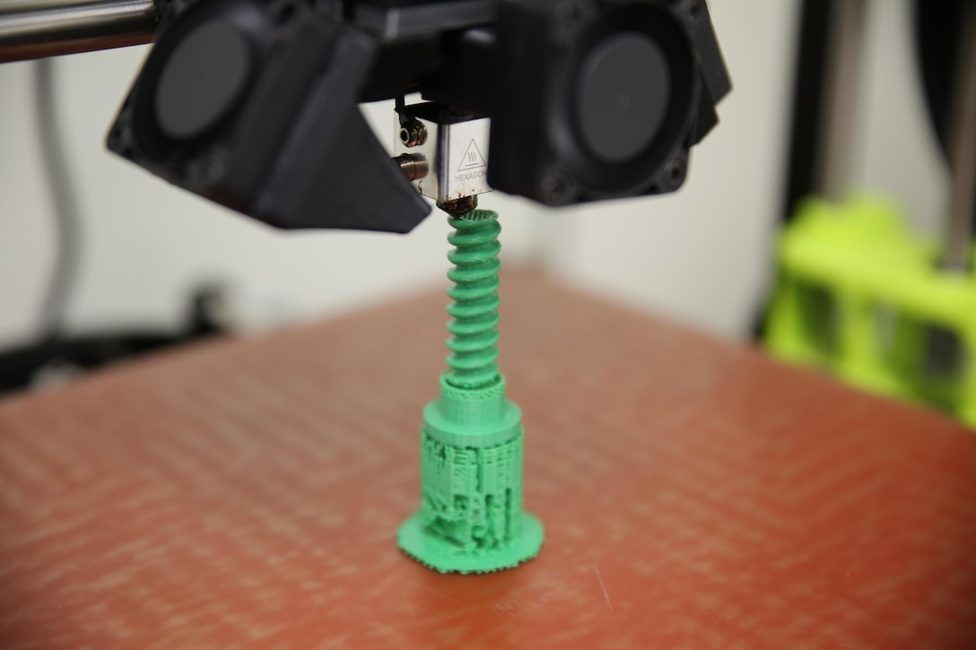 A 3-D desktop printer creates a screw at the X-FAB, or Expeditionary Fabrication, Facility Aug. 1 at Camp Lejeune, North Carolina. X-FAB is a self-contained, transportable additive manufacturing lab comprised of a 20-by-20-foot shelter, 3-D printers, a scanner and computer-aided design software system that can be used to fabricate repair and replacement parts in the field. The Marine Corps is using an X-FAB located with the 2nd Maintenance Battalion at Camp Lejeune, North Carolina, to explore this expeditionary capability. If acquired, the system can help expedite heavy equipment repairs in deployed environments. (U.S. Marine Corps photo by Monique Randolph)