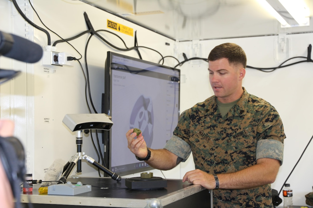 Sgt. Ethan Maeder, a machinist with the 2nd Maintenance Battalion at Camp Lejeune, North Carolina, demonstrates how to use a 3-D scanner in the X-FAB Facility Aug. 1. The X-FAB, or Expeditionary Fabrication, Facility is a self-contained, transportable additive manufacturing lab comprised of a 20-by-20-foot shelter, 3-D printers, a scanner and computer-aided design software system that can be used to fabricate repair and replacement parts in the field. The Marine Corps is exploring this expeditionary capability to expedite heavy equipment repairs in deployed environments. (U.S. Marine Corps photo by Kaitlin Kelly)