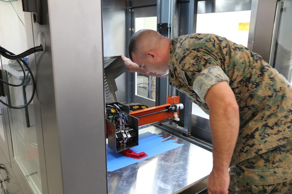 Gunnery Sgt. Doug McCue, a machinist with the 2nd Maintenance Battalion at Camp Lejeune, North Carolina, demonstrates the capabilities of a large-build 3-D printer in the X-FAB Facility Aug. 1. The X-FAB, or Expeditionary Fabrication, Facility is a self-contained, transportable additive manufacturing lab comprised of a 20-by-20-foot shelter, 3-D printers, a scanner and computer-aided design software system that can be used to fabricate repair and replacement parts in the field. The Marine Corps is exploring this expeditionary capability to expedite heavy equipment repairs in deployed environments. (U.S. Marine Corps photo by Kaitlin Kelly)