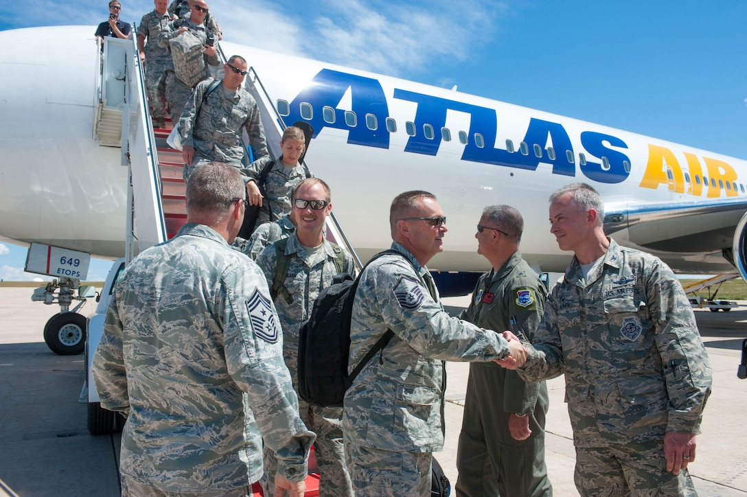 Commanders greeting Airmen as they come off airliner