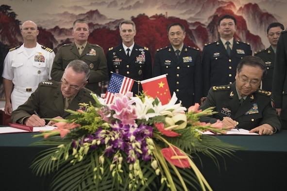 Military leaders sign an agreement.