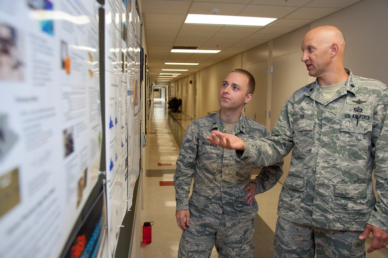 WRIGHT-PATTERSON AIR FORCE BASE, Ohio – Lt. Col. James Fee, Air Force Institute of Technology assistant professor of nuclear engineering, discusses electromagnetic pulse and how to model it from a nuclear weapon with 1st. Lt. Cameron Merriman, an AFIT student, June 22 using a display board hung in one of AFIT's corridors. (U.S. Air Force photo/John Harrington)