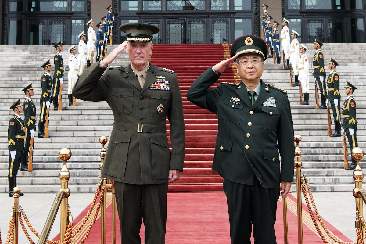 Marine Corps Gen. Joe Dunford stands next to Chinese Army Gen. Fang Fenghui as both leaders salute.