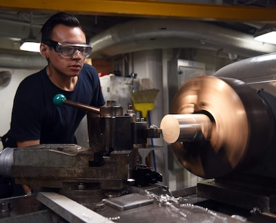 Navy Petty Officer 3rd Class Kody Kratz uses a lathe to turn down an aluminum carbide turning tube aboard the aircraft carrier USS George H.W. Bush