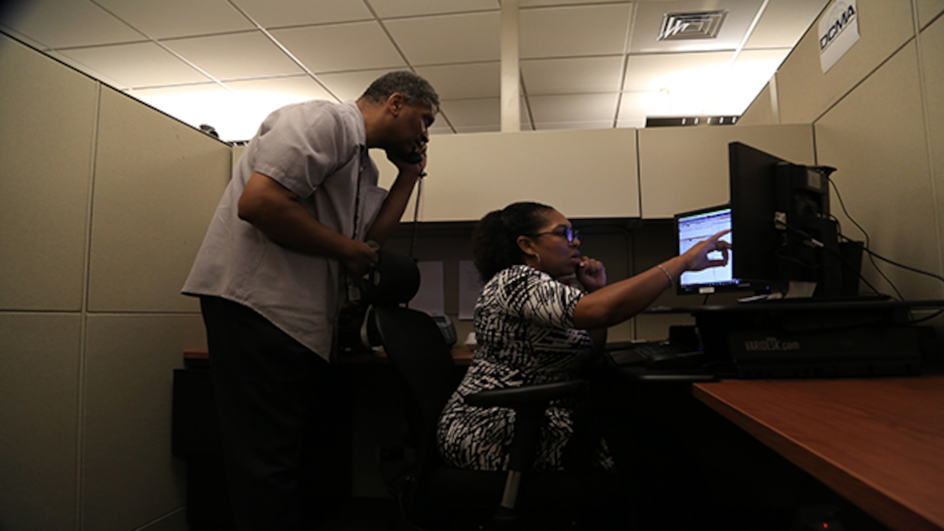 Defense Contract Management Agency video teleconferencing professionals, Terence Arrington and April Schulter, manage multipoint conferences during the global all hands from Fort Lee, Virginia, July 26, 2017. (DCMA photo by Elizabeth Szoke)