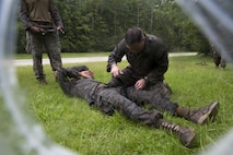 A Marine applies a tourniquet to a notional casualty during a casualty care evaluation as part of the 2nd Light Armored Reconnaissance Isaak Competition at Camp Lejeune, N.C., August 8, 2017. The Isaak Competition, in honor of Cpl. Garreth Isaak, distinguishes the most proficient scout within the Battalion through a series of events including an endurance course, land navigation, and weapons proficiency. The Marines are with 2nd LAR Battalion. (U.S. Marine Corps photo by Lance Cpl. Gloria Lepko)