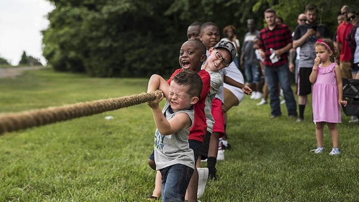 Children pull a rope during a tug of war match while a crowd watches.
