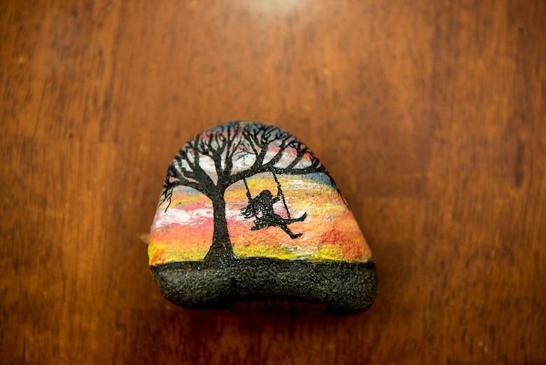 Members of PAFB rocks! paint rocks to display and hide around Peterson Air Force Base, Colo., for others to find. Aug. 4, 2017. This rock was painted by Andrea Collis depicting a girl swinging on a tree during a sunset. (U.S. Air Force photo by Steve Kotecki)