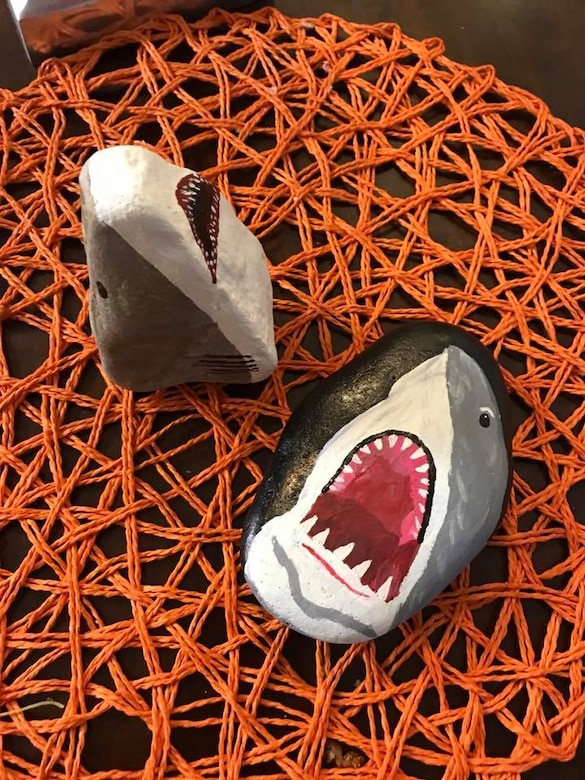 Vanessa Legaspi Henneman finishes painting shark rocks and then hid them on Peterson Air Force Base, Colo., Aug. 4. 2017. The group will often pick a theme for the week and paint rocks in that theme. The theme for the week of July 31, was based on TV's shark week. (Courtesy photo by Vanessa Legaspi Henneman)