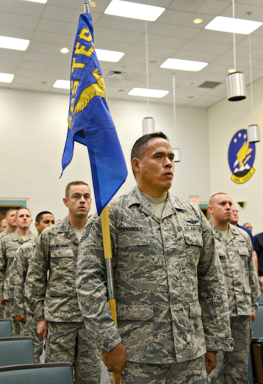Tech. Sgt. Kamanu Fernandez, test flight engineer and additional duty first sergeant, holds the newly unfurled guidon for the 605th Test and Evaluation Squadron, Detachment 1, while in formation with his squadron during a ceremony Aug. 7, 2017, in Fannin Hall.