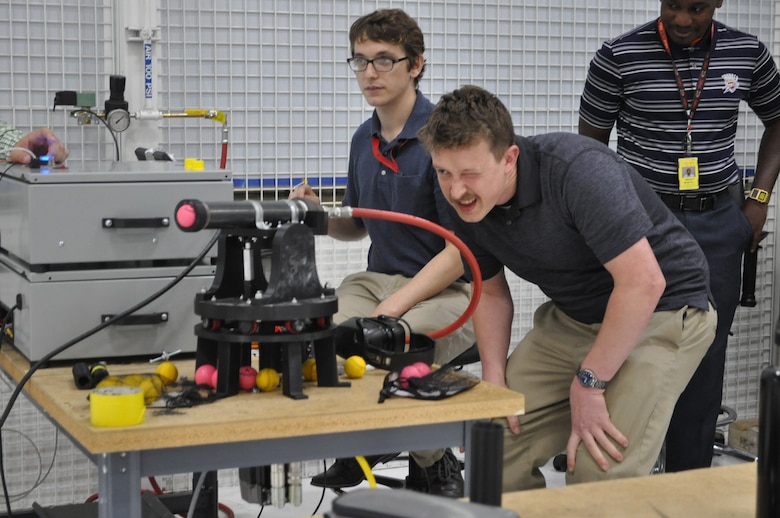 Intern Michael Fleagle eyeballs the trajectory of an air cannon that fires practice golf balls at targets in a competition set up by the 555th Software Maintenance Squadron in Bldg. 9001.