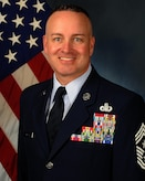 Biography photo of Chief Master Sgt. David R. Wolfe with U.S. flag in background
