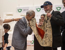 Tatsuya Yasue, left, receives a flag from World War II veteran Marvin Strombo at Higashishirakawa Village, Gifu Prefecture, Japan, Aug. 15, 2017.