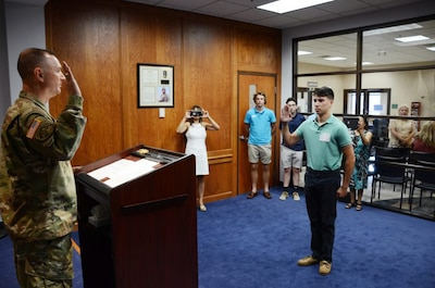 Army Col. James Ring, chief of staff for the Virginia Army National Guard, enlists Pvt. Paul David Kelly into the Virginia Army National Guard at Fort Lee, Va., July 26, 2017. Kelly is the son of fallen Virginia Army National Guard Col. Paul M. Kelly, who was killed in a helicopter crash in Iraq in 2007. Virginia Army National Guard photo by Sgt. 1st Class Terra C. Gatti