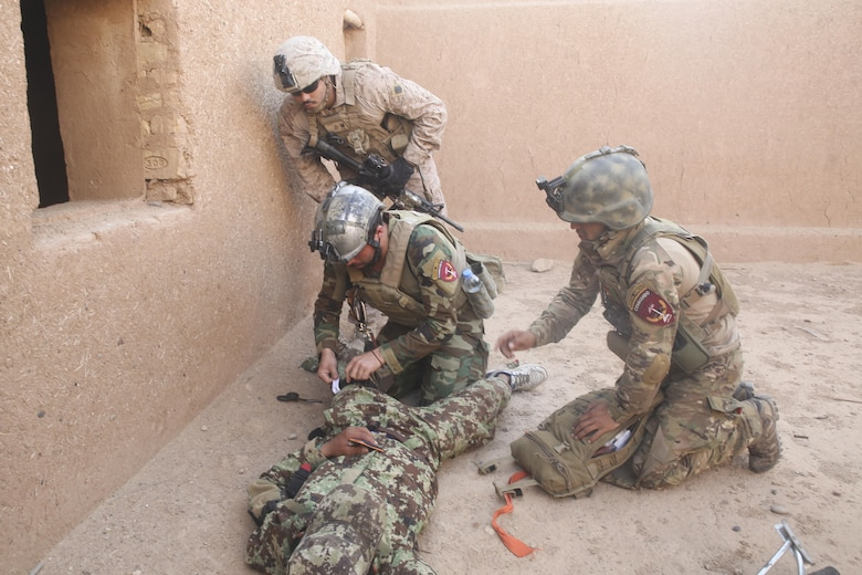An Afghan National Army soldier with 215th Corps applies a tourniquet to a notionally-injured soldier during casualty evacuation training at Camp Shorabak, Afghanistan, Aug. 14, 2017. Several ANA units practiced their CASEVAC procedures in preparation for future real-world operations. Quickening the CASEVAC process vastly improves survivability and recovery rates for wounded personnel. (U.S. Marine Corps photo by Sgt. Lucas Hopkins)