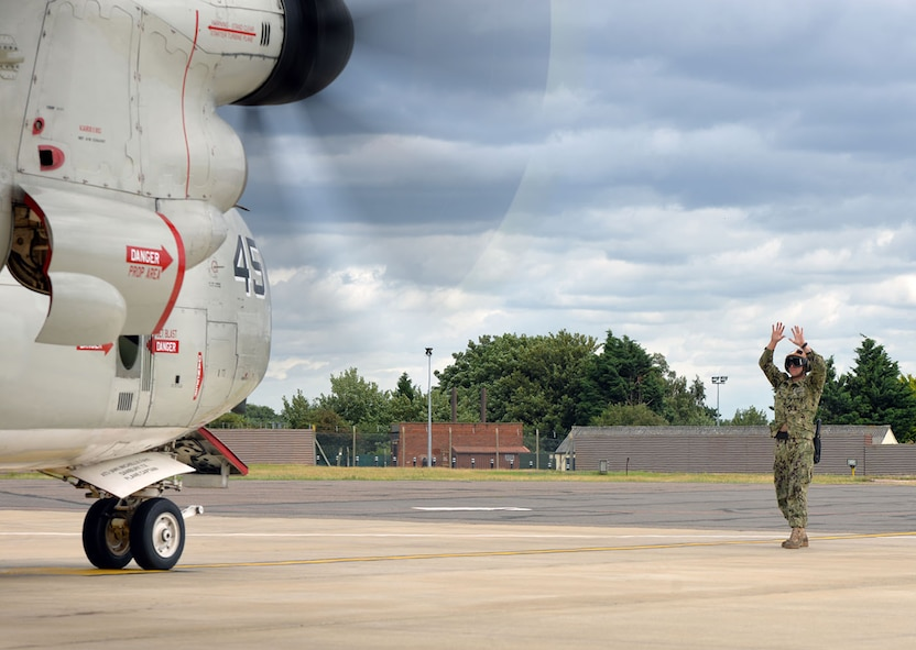 U.S. Navy Petty Officer 2nd Class Seth Neighbor, VRC-40 Naval aircrewman mechanical, gives marshalling signals to the pilots of a C-2A Greyhound on RAF Mildenhall, England, as they prepare to take off on a mission to the USS George H.W. Bush aircraft carrier (CVN77) Aug. 3, 2017. Two C-2A aircraft were TDY to RAF Mildenhall as part of Exercise Saxon Warrior, a multinational joint maritime exercise involving 15 warships from five different nations, along with submarines, more than 100 aircraft and approximately 9,000 personnel. (U.S. Air Force photo by Karen Abeyasekere)