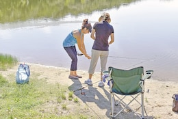 Layla Romero, a family life administrative assistant for the Fort Riley Garrison Religious Support Office, helps Eunice Min get ready for a bit of fishing at Moon Lake during the 242nd Chaplain Corps Anniversary Celebration, July 28.
