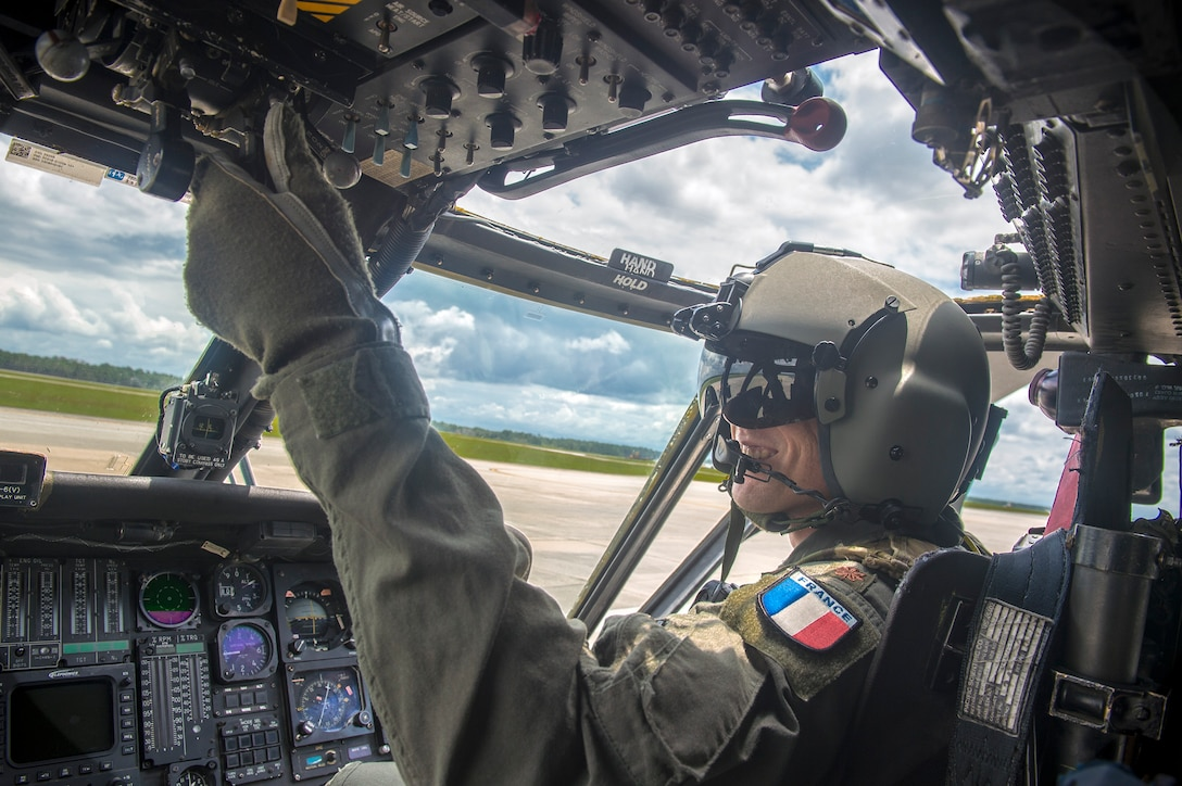 Commandant Micka, a French exchange pilot and assistant director of operations for Moody's 41st Rescue Squadron, actuates switches in a HH-60G Pavehawk, Aug. 2, 2017, at Moody Air Force Base, Ga. Prior to his arrival at the 41st RQS, Micka transitioned from flying the French Air Force's EC-725 Caracal helicopter to learn the HH-60. Since his childhood, Micka aspired to serve and fly for the French and U.S. military as a rescue pilot. (U.S. Air Force photo by Senior Airman Greg Nash)