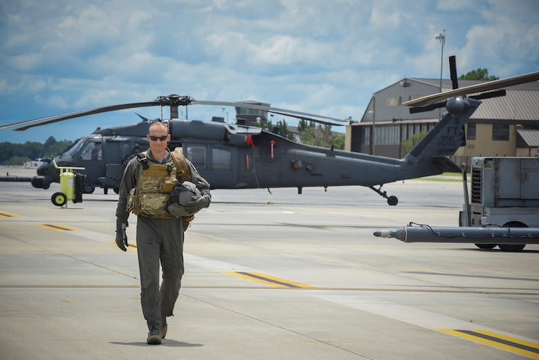 Commandant Micka, a French exchange pilot and assistant director of operations for Moody's 41st Rescue Squadron, walks on the flightline past an HH-60G Pavehawk, Aug. 2, 2017, at Moody Air Force Base, Ga. Prior to his arrival at the 41st RQS, Micka transitioned from flying the French Air Force's EC-725 Caracal helicopter to learn the HH-60. Since his childhood, Micka aspired to serve and fly for the French and U.S. military as a rescue pilot. (U.S. Air Force photo by Senior Airman Greg Nash)