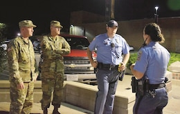 Sgt. 1st. Class Kyle Weber, front left, Sgt. 1st Class Chris Taylor, back left, both of 1st Squadron, 4th Cavalry Regiment, 1st Armored Brigade Combat Team, 1st Infantry Division; Garrett Lloyd, back right, and Rachel Pate, Riley County Police Department patrol officers, discuss their next line of action Aug. 4 in Aggieville in Manhattan, Kansas.