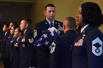 Master Sgt. Jason Burdett, 81st Security Forces squadron first sergeant, participates in a passing of the flag ceremony during a retirement ceremony for Chief Master Sgt. Vegas Clark, former 81st Training Wing command chief, in the Bay Breeze Event Center Aug. 11, 2017, on Keesler Air Force Base, Miss. Clark retired with 22 years of military service. Prior to his assignment at Keesler he served as the command chief for the 39th Air Base Wing, Incirlik Air Base, Turkey. (U.S. Air Force photo by Kemberly Groue)
