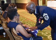 Chief Master Sgt. Vegas Clark, former 81st Training Wing command chief, presents the U.S. flag to his mother, Rochelle Randol, during his retirement ceremony in the Bay Breeze Event Center Aug. 11, 2017, on Keesler Air Force Base, Miss. Clark retired with 22 years of military service. Prior to his assignment at Keesler he served as the command chief for the 39th Air Base Wing, Incirlik Air Base, Turkey. (U.S. Air Force photo by Kemberly Groue)