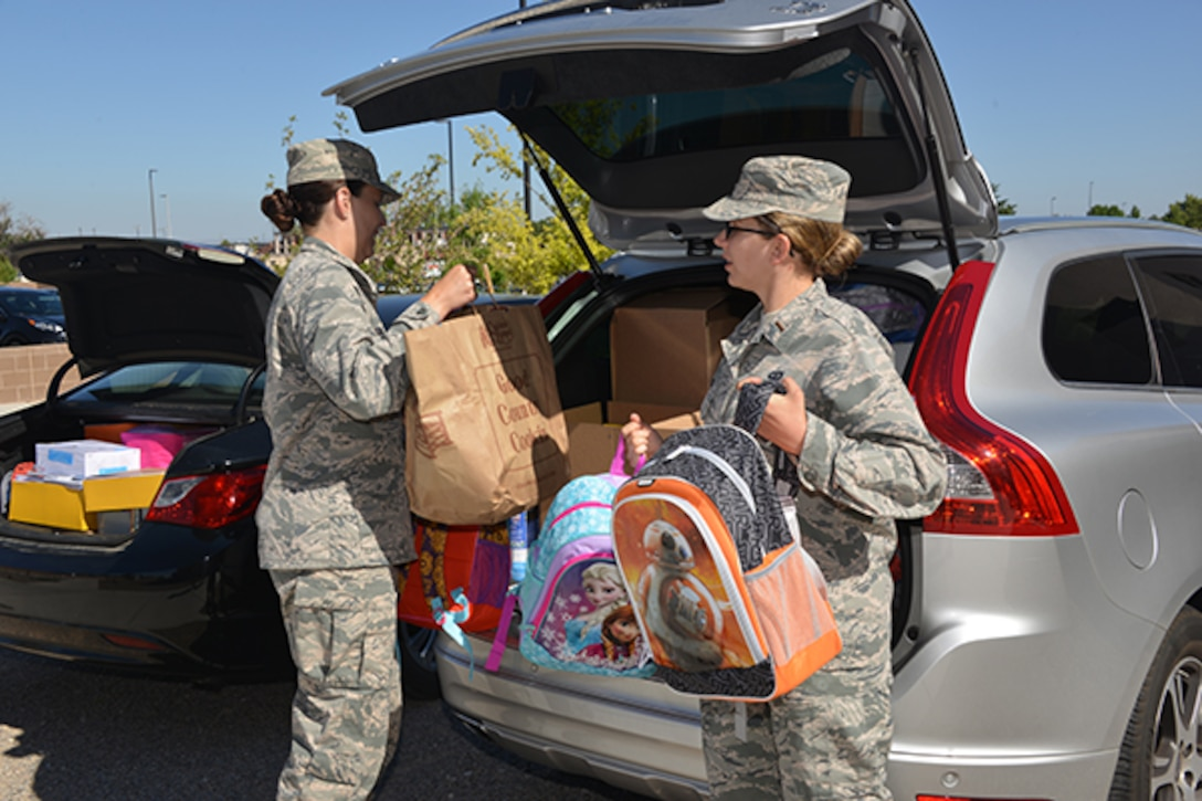 1st Lt. Christiana Fairman and 2nd Lt. Billie DeLuca of the Air Force Nuclear Weapons Center load more than $3,500 in donated school supplies from AFNWC for delivery to three local Title-I schools.