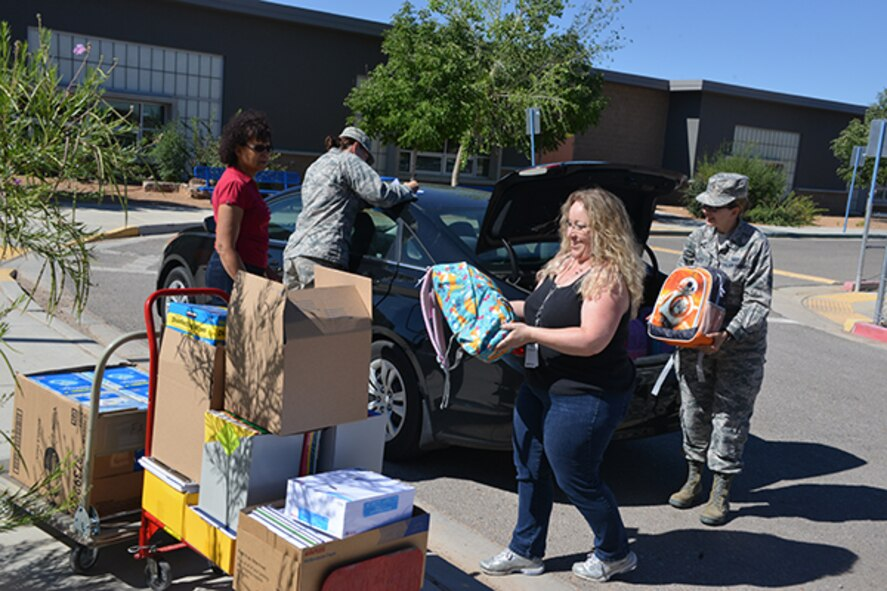 Volunteers from the Air Force and local communities unload supplies donated to the Title-I school for the upcoming year.