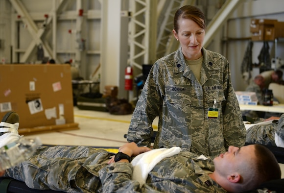 Lt. Col. Catherine Bonhoff, 375th Aeromedical Evacuation Squadron Director of Operations, talks with a simulated patient during Exercise Mobility Guardian at Joint Base Lewis-McChord, Wash.