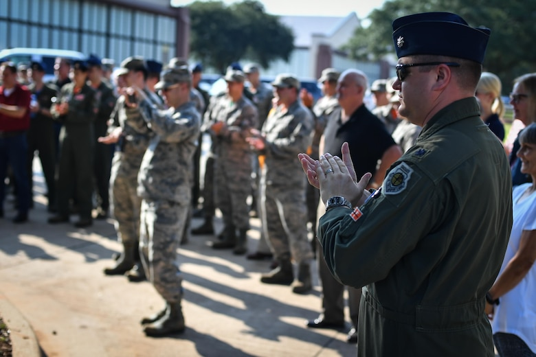 Members of the 49th Test and Evaluations Squadron, both past and present applaud during the unveiling of a monument celebrating the squadron's 100th anniversary at Barksdale Air Force Base, La., Aug. 2, 2017. The squadron's main focus is on the B-52 Stratofortress with additional testing being conducted on the B-1 and B-2. Additionally, in its 100 years in service, the squadron also performed test on other bombers such as the B-17 Flying Fortress, B-29 Superfortress, B-29 Superfortress and others. (U.S. Air Force Photo/Senior Airmen Mozer O. Da Cunha)