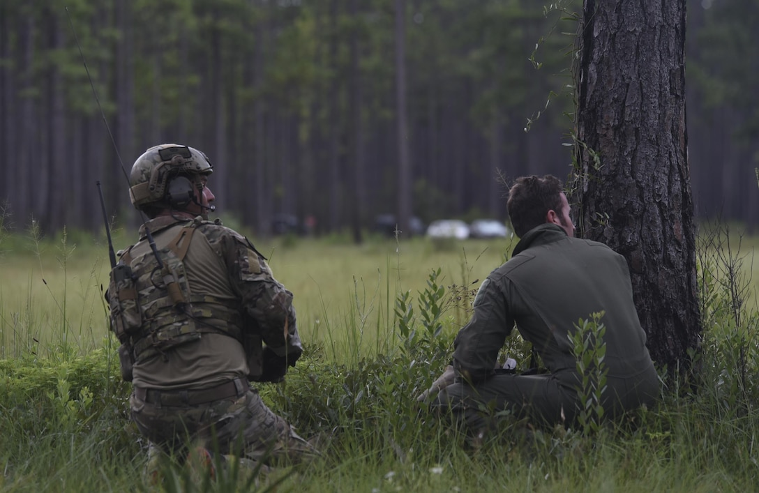 A U.S. Air Force Survival, Evasion, Resistance and Escape technician from Moody Air Force Base, Ga., (Left) and a simulated downed F-22 Raptor pilot from Tyndall Air Force Base, Fla., watch as an HH-60G Pave Hawk flies into a landing zone in wooded area near Tyndall, during exercise Stealth Guardian Aug. 8, 2017.