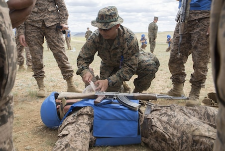 U.S. Navy Petty Officer 1st Class Benjamin Guinto demonstrates how to apply a bandage for a practical application of tactical combat casualty care during Exercise Khaan Quest 2017 at Five Hills Training Area, Mongolia, July 24, 2017. Khaan Quest 2017 is a Mongolian-hosted, combined, joint training exercise designed to strengthen the capabilities of the U.S., Mongolia and other partner nations in international peacekeeping operations. Guinto, from Hawthorne, California is a ¬¬¬corpsman with 3rd Medical Battalion, 3rd Marine Logistics Group, III Marine Expeditionary Force. (U.S. Marine Corps photo by Lance Cpl. Charles Plouffe)