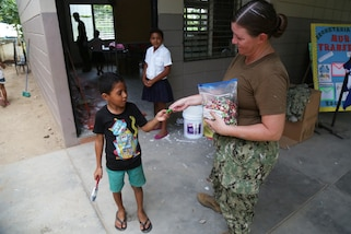 A U.S. Navy Sailor hands out candy to students during a Southern Partnership Station 17 community relations project at a Honduran elementary school