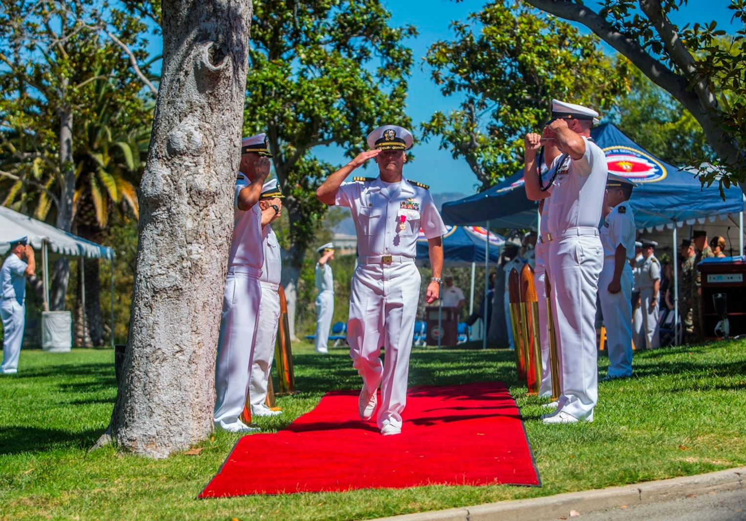 """U.S. Navy Capt. Peter A. Ruocco returns a salute and departs from the 1st Dental Battalion change of charge ceremony at Camp Pendleton, Calif., Aug. 16, 2017. During Ruocco's departure, the sideboys render their honors as the boatswain """"pipes"""" Ruocco ashore. The Boatswains pipe is traditionally used to pass commands to the crew as the sound of the crew or bad weather would drown out a Sailors voice. (U.S. Marine Corps photo by Lance Cpl. Joseph Sorci)"""