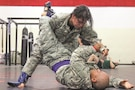 Spc. Noemi Mendez with the 97th Military Police Battalion, 89th Military Police Brigade, practices take-down maneuvers with Staff Sgt. Rafael Verdejo, Headquarters and Headquarters Battalion, 1st Infantry Division, during a combatives drill Aug. 7 at Long Fitness Center. A combatives tournament will be part of the Commander's Cup challenge during Victory Week 2017.