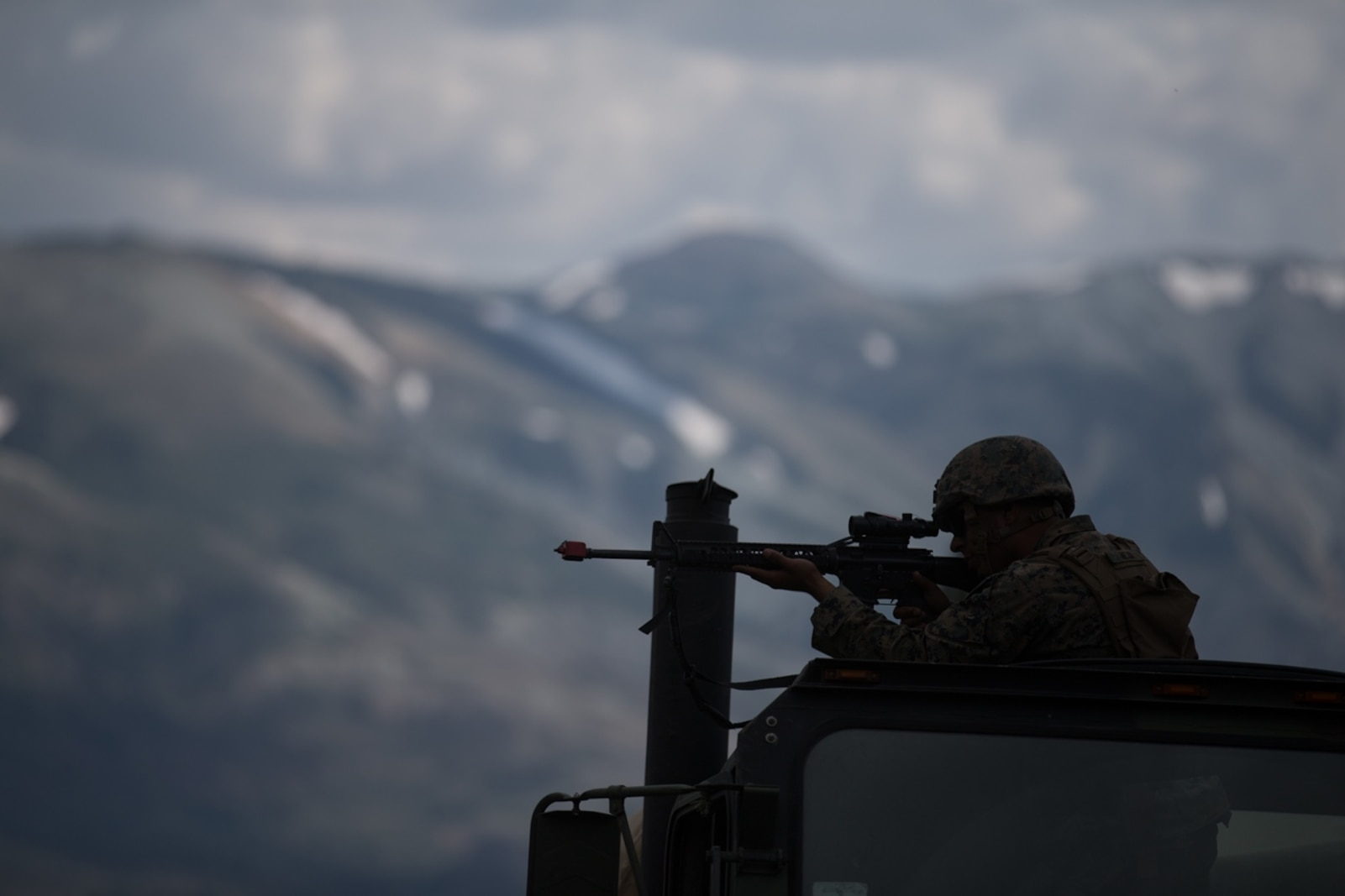 U.S. Marine Lance Cpl. Luis Mejia, a motor transportation operator with Combat Logistics Battalion 5, Combat Logistics Regiment 1, 1st Marine Logistics Group, posts security while participating in a convoy during Mountain Training Exercise 4-17 at Mountain Warfare Training Center, August 6, 2017. Marines participating in the Mountain Training Exercise post security to demonstrate protecting various areas against any possible simulated attack or ambush in the mountainous terrain. (U.S. Marine Corps photo by Lance Cpl. Timothy Shoemaker)