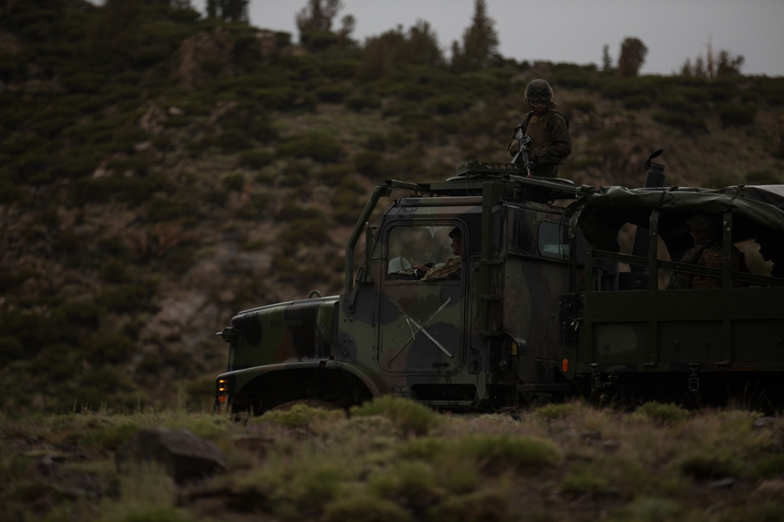 U.S. Marines and Sailors with Combat Logistics Battalion 5, Combat Logistics Regiment 1, 1st Marine Logistics Group, participate in a convoy during Mountain War Training 4-17 at Mountain Warfare Training Center, August 5, 2017. Most 7-ton vehicles have a Marine Rifleman positioned on top of the roof to act as an observer. (U.S. Marine Corps photo by Lance Cpl. Timothy Shoemaker)