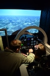 Maj. Andrew Rose, an instructor pilot with the 559th Flying Training Squadron assists his daughter Amber in a T-6A Texan II flight simulator as part of the unit's bring your kids to work day, Joint Base San Antonio-Randolph, Texas, Aug 11, 2017. The simulator gave the kids an opportunity to fly around without leaving the ground. (U.S. Air Force photo by Tech. Sgt. Ave I. Young)