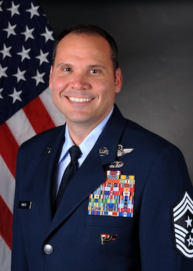 Official bio photo of man in Air Force Blues standing in front of the American Flag. The man is ranked Command Chief Master Sergeant.