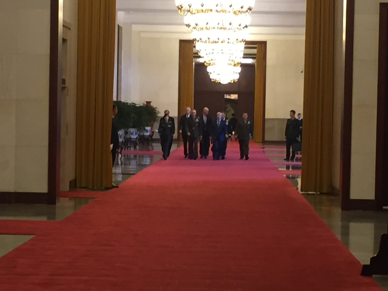 The chairman of the Joint Chiefs of Staff, walks with his team through the Great Hall of the People in Beijing.