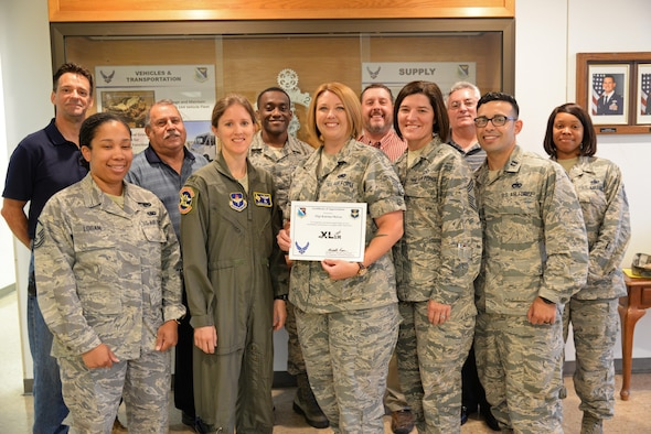 Staff Sgt. Katrina McGee, 47th Logistics Readiness Squadron plans and integration NCOIC, presents her award from wing leadership Aug. 14.