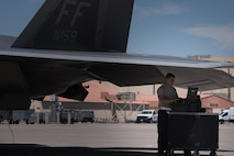 U.S. Air Force Airman Juan Luna, 94th Aircraft Maintenance Unit crew chief, reviews technical orders, while preparing to launch an F-22 Raptor during Red Flag 17-4, at Nellis Air Force Base, Nev. , Aug. 14, 2017. (U.S. Air Force photo/Staff Sgt. Carlin Leslie)