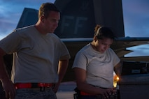 U.S. Air Force Staff Sgt. Christopher Wilson and Senior Airman Maza Nurya, 27th Aircraft Maintenance Unit crew chiefs, review technical orders for the F-22 Raptor, while preparing to launch aircraft during Red Flag 17-4, at Nellis Air Force Base, Nev. Aug. 14, 2017. (U.S. Air Force Photo/Staff Sgt. Carlin Leslie)