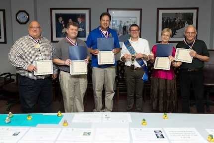 (From left to right) Defense Language Institute instructors David Britton, Chad Hamilton, Chad Kallauner, Reza Keivanzadeh, Carole Franki, and Earl Gaston pose for a group photo with their awards Aug. 4, 2017 at Joint Base San Antonio-Lackland, Texas. The instructors each received an award for an eternal safety campaign they held in conjunction with their 101 Critical Days of Summer Safety brief. Keivanzadeh received a trophy for having the highest unit participation.