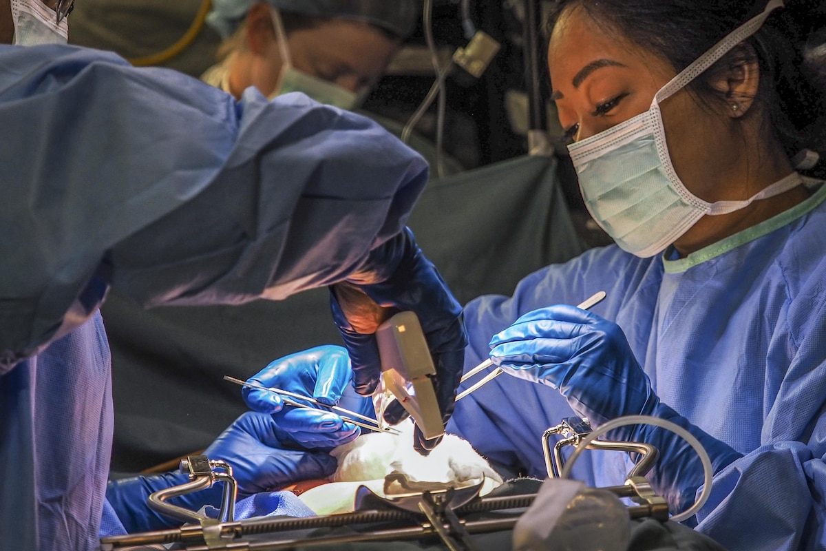Airmen in blue gowns and masks train during a simulated surgery as part of an exercise.