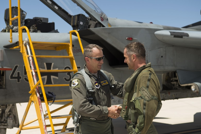 Col. James Keen, 54th Fighter Group commander, coins Maj. Lars Parlow, German air force Tornado pilot, at Holloman Air Force Base, Aug. 17, 2017. The GAF has entered its final stage of departure, however they will not complete their departure from Holloman until mid 2019. (U.S. Air Force photo Tech. Sgt. Amanda Junk)
