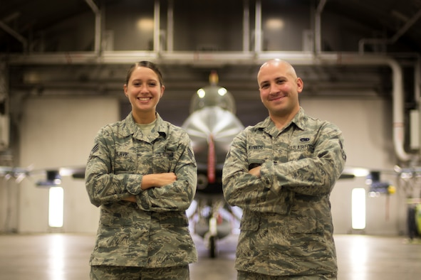 U.S. Air Force Senior Airman Amber Slavik, left, a 35th Medical Support Squadron medical logistics technician, and Airman 1st Class Anthony Kovacs, Jr., right, a 14th Fighter Squadron crew chief, pose in front of an F-16 Fighting Falcon at Misawa Air Base, Japan.