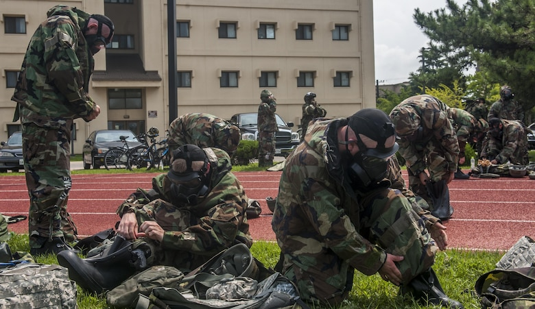 U.S. Air Force Airmen assigned to the 8th Fighter Wing, practice donning protective Mission Oriented Protective Posture gear during a wing training day at Kunsan Air Base, Republic of Korea, Aug. 18, 2017. The day focused on Ability To Survive and Operate training, self-defense and Self Aid Buddy Care. (U.S. Air Force photo by Senior Airman Colville McFee)