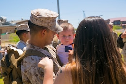 Sgt. Krystian Madrid, intelligence specialist, 7th Marine Regiment, holds his son following his unit's homecoming at Victory Park aboard the Marine Corps Air Ground Combat Center, August 17, 2017. 7th Regiment Marines completed a nine month deployment as the command element of Special Purpose Marine Air-Ground Task Force – Crisis Response – Central Command 17.1.